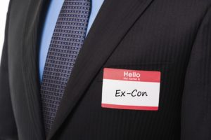 Red Hello My Name Is sticker name tag on man in suit and tie with blue shirt